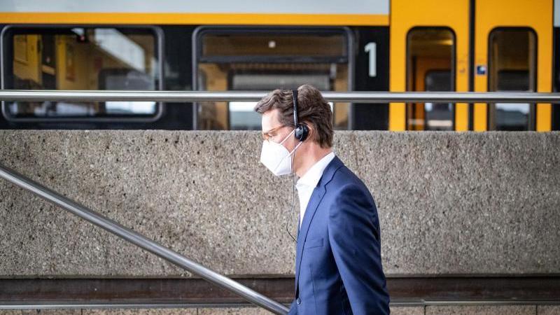 Hendrik Wüst (l,CDU), Verkehrsminister von NRW, geht im Hauptbahnhof eine Treppe hinauf.. Foto: Marcel Kusch/dpa
