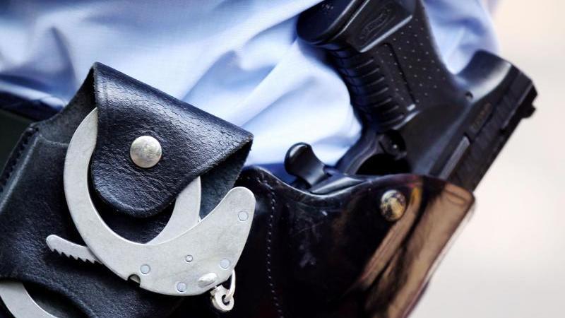 Ein Polizist mit Handschellen und Pistole am Gürtel. Foto: picture alliance / dpa / Symbolbild