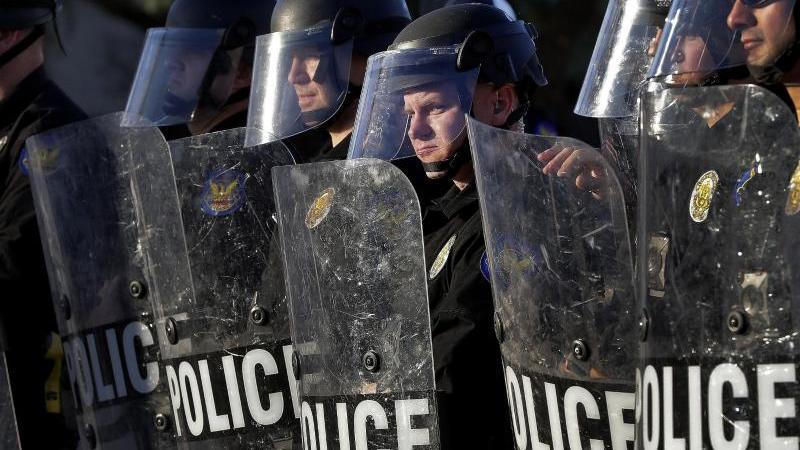 Polizisten beobachten in Phoenix einen Protestmarsch. Foto: Matt York/AP/dpa