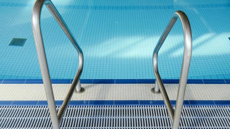 Eine Leiter ist im Hallenbad vor dem leeren Schwimmerbecken zu sehen. Foto: Uwe Anspach/dpa