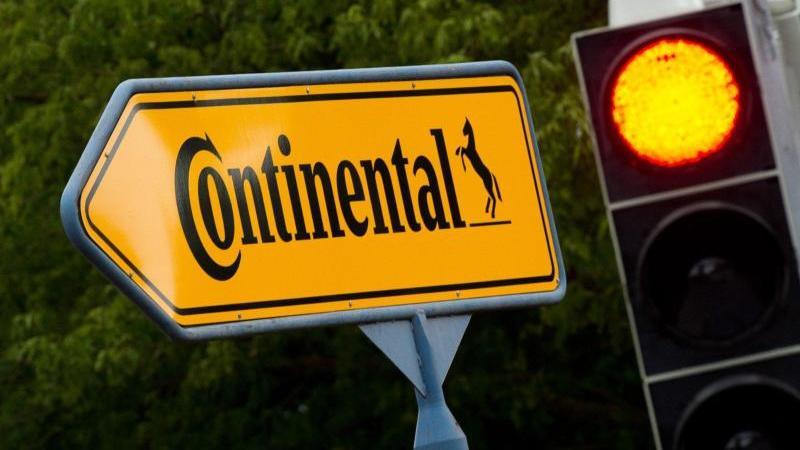 """Ein rote Ampel leuchtet neben einem Schild mit der Aufschrift """"Continental"""". Foto: Julian Stratenschulte/dpa/Archivbild"""