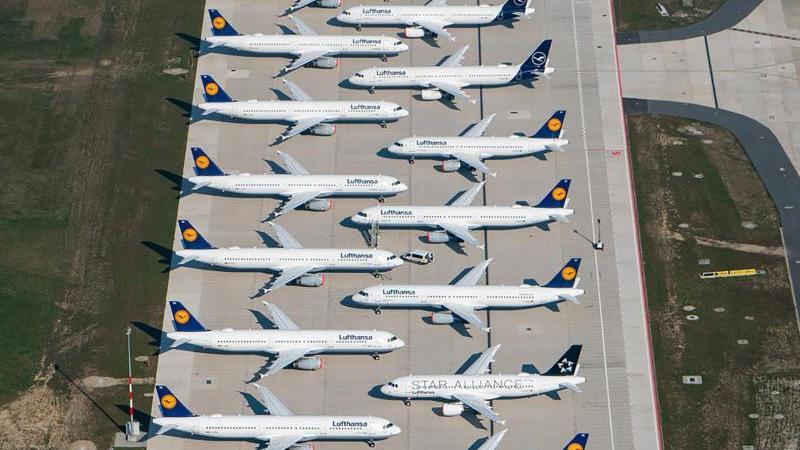 Maschinen der Fluggesellschaft Lufthansa stehen abseits der Start- und Landebahn. Foto: Tino Schöning/dpa-Zentralbild/dpa/Archivbild