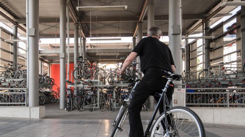 Ein Mann verlässt mit seinem Fahrrad ein Fahrradparkhaus