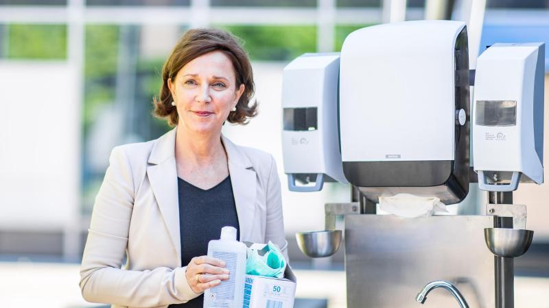 Die nordrhein-westfälische Schulministerin Yvonne Gebauer (FDP) steht neben einem Spender für Wasser, Papierhandtücher und Seife, während sie Desinfektionsmittel, Handschuhe und Masken in den Händen hält. Foto: Marcel Kusch/dpa/Archivbild