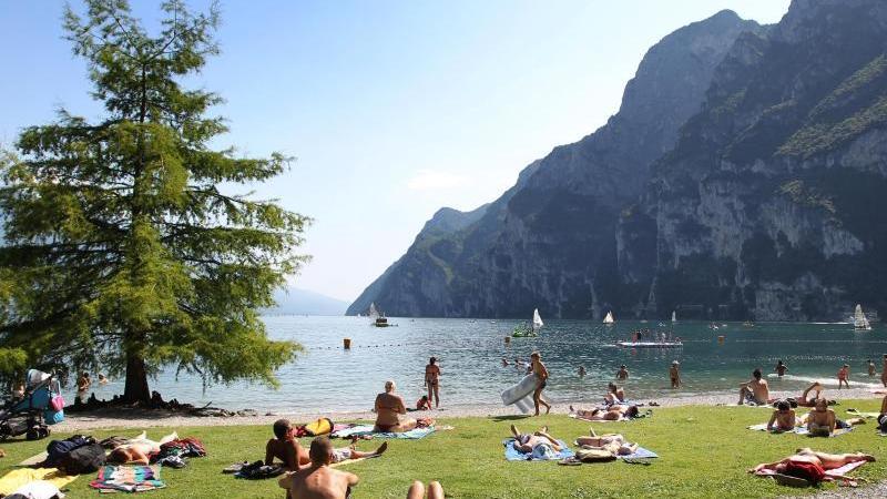 Touristen und Einheimische nehmen am Strand von Riva del Garda ein Sonnenbad. Foto: picture alliance / dpa / Archivbild