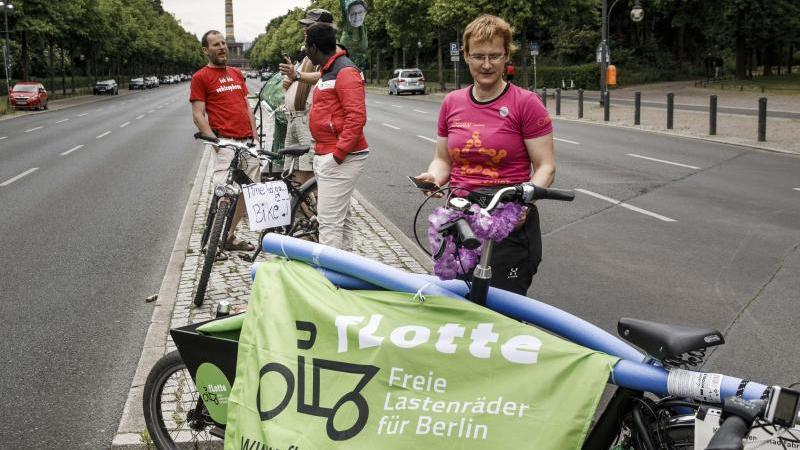 Teilnehmer der Aktion des ADFC stehen mit ihren Fahrräder auf der Straße des 17. Juni. Foto: Carsten Koall/dpa