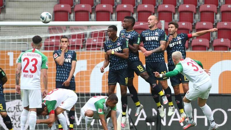 FC Augsburgs Philipp Max schießt den Freistoß über die Mauer aufs Tor. Foto: Michael Dalder/Reuters-Pool/dpa