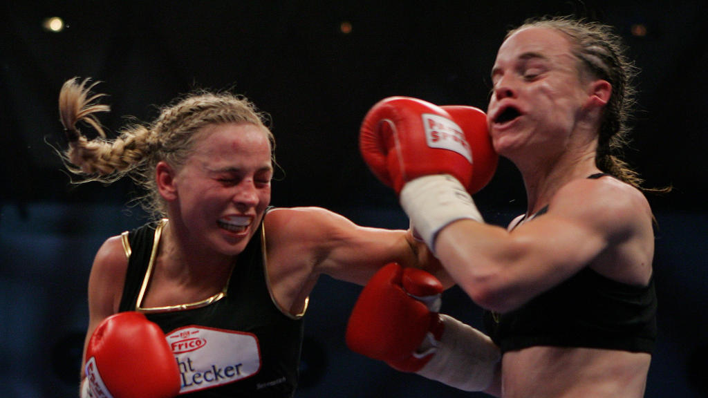 KARLSRUHE, GERMANY - NOVEMBER 30:  Regina Halmich of Germany (L) lands a punch against Hagar Shmoulefeld Finer of Israel during their WIBF World Championship flyweight title fight at the DM Arena on November 30, 2007 in Karlsruhe, Germany. Halmich, w