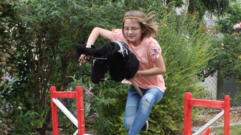 Die zehnjährige Melina Gardt beim Reittraining mit dem Steckenpferd. Foto: Tina Gardt/dpa