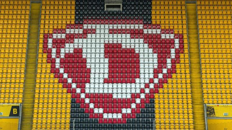 Das Logo von Dynamo Dresden ist auf der Tribüne auf gelben und schwarzen Sitzen zu sehen. Foto: Robert Michael/dpa-Zentralbild/dpa/Archivbild