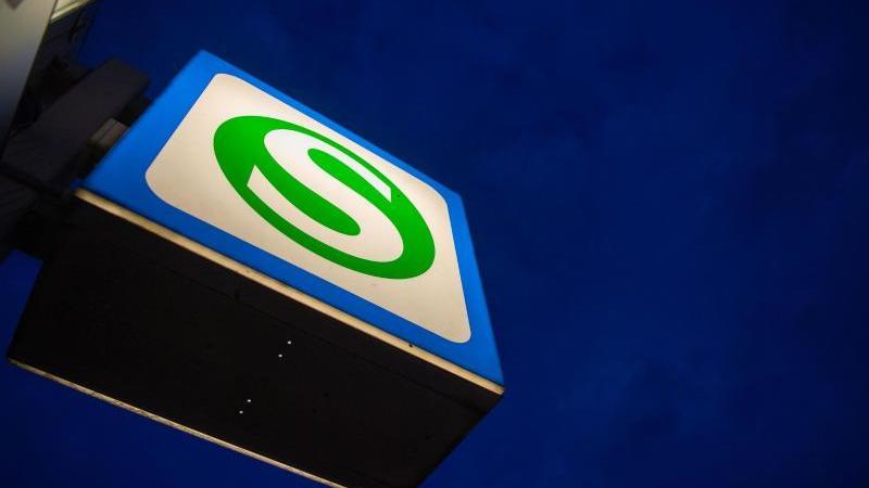 Ein S-Bahn-Schild hängt an einer Station vor dem dunklen Morgenhimmel. Foto: Lino Mirgeler/dpa/Archivbild