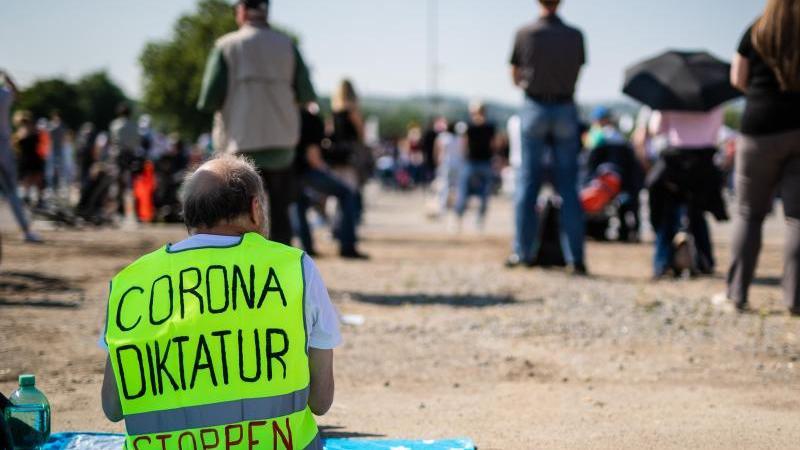 """Ein Demonstrant trägt eine Warnweste mit der Aufschrift """"Corona Diktatur stoppen"""". Foto: Christoph Schmidt/dpa/Archivbild"""
