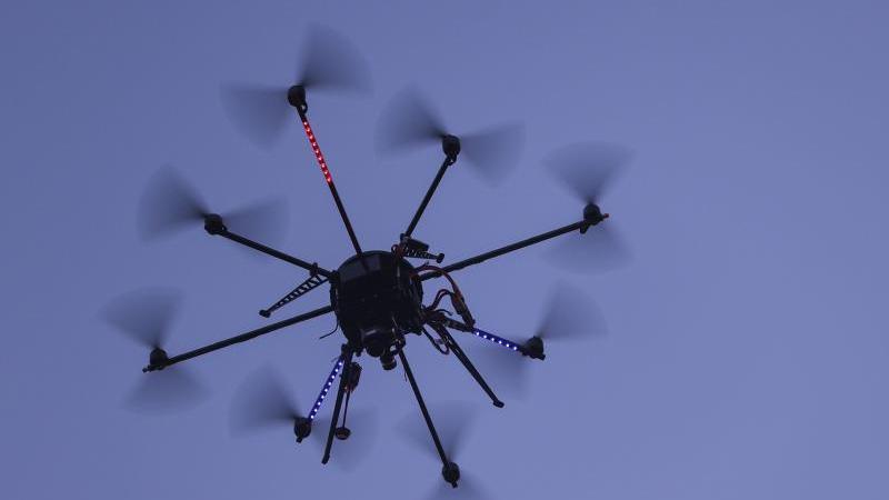 Ein Drohne fliegt am blauen Himmel. Foto: Jens Büttner/dpa-Zentralbild/dpa/Archivbild