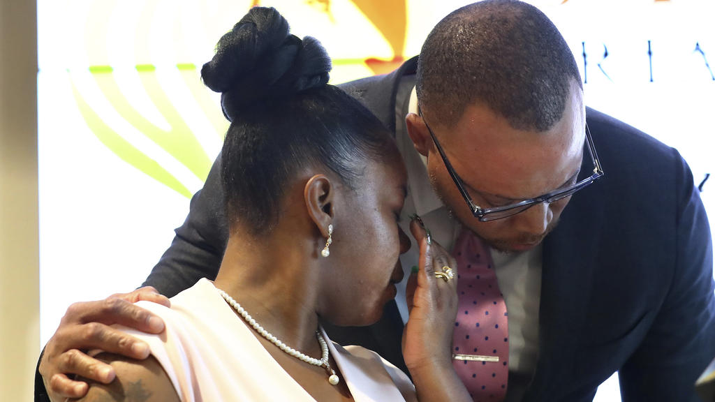 Rayshard Brooks' widow Tomika Miller is comforted by attorney Justin Miller while addressing the media Wednesday, June 17, 2020, in Atlanta, after learning new details of her husband's death. The Fulton County District Attorney Paul Howard had just a