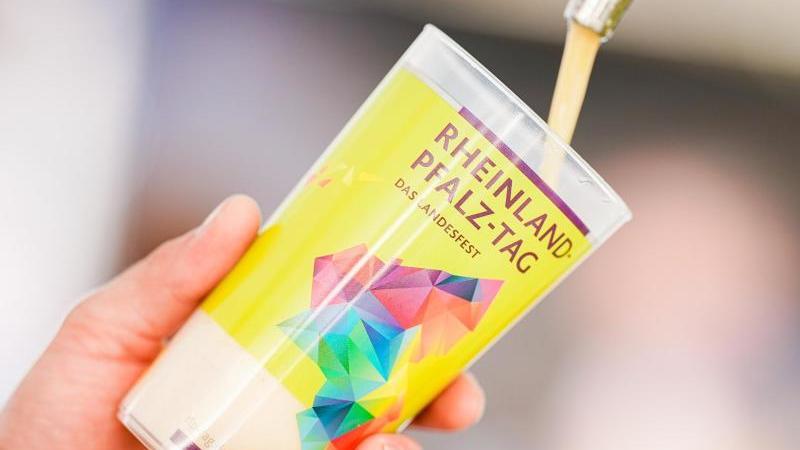 """Ein Becher mit der Aufschrift """"Rheinland-Pfalz-Tag"""" wird unter einen Zapfhahn gehalten. Foto: Uwe Anspach/dpa/Symbolbild"""