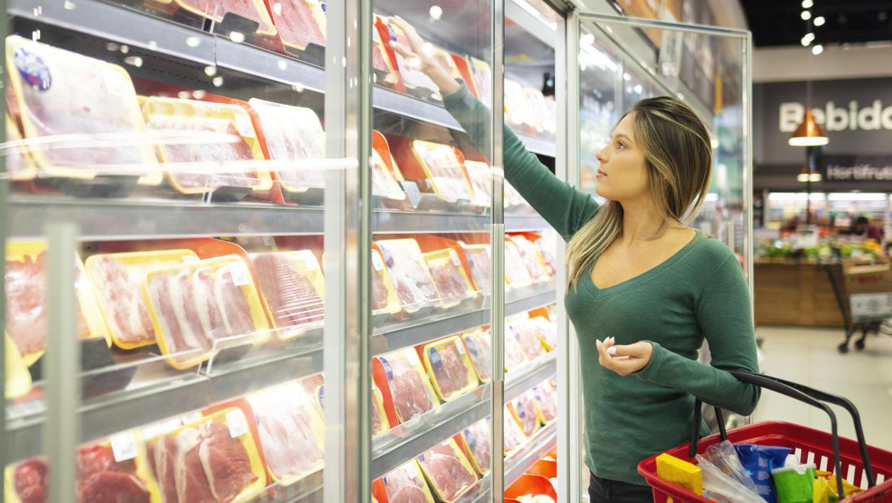 Junge Frau im Supermarkt kauft Fleisch
