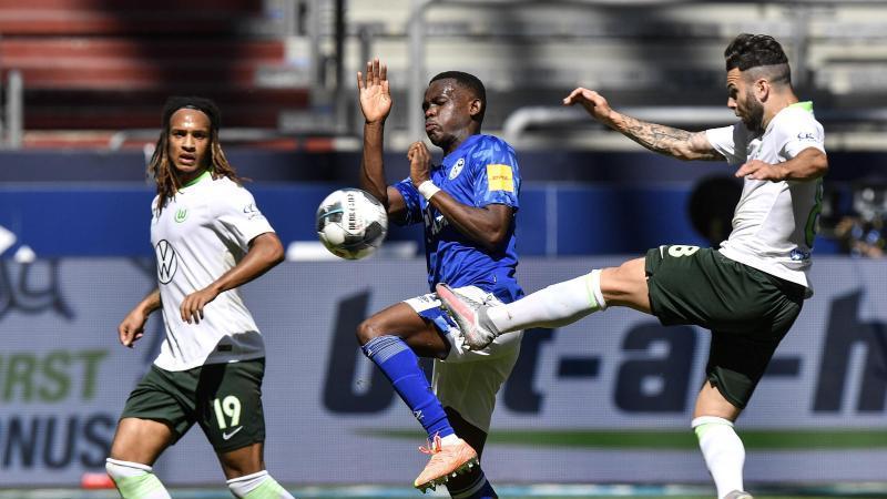 Rabbi Matondo (M) vom FC Schalke 04 und Renato Steffen (r) vom VfL Wolfsburg kämpfen um den Ball. Foto: Martin Meissner/AP-Pool/dpa