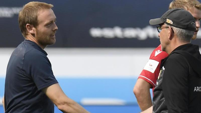 Union-Trainer Urs Fischer (r) gratuliert TSG-Trainer Matthias Kaltenbach zum Sieg seiner Mannschaft. Foto: Thomas Kienzle/AFP Pool/dpa