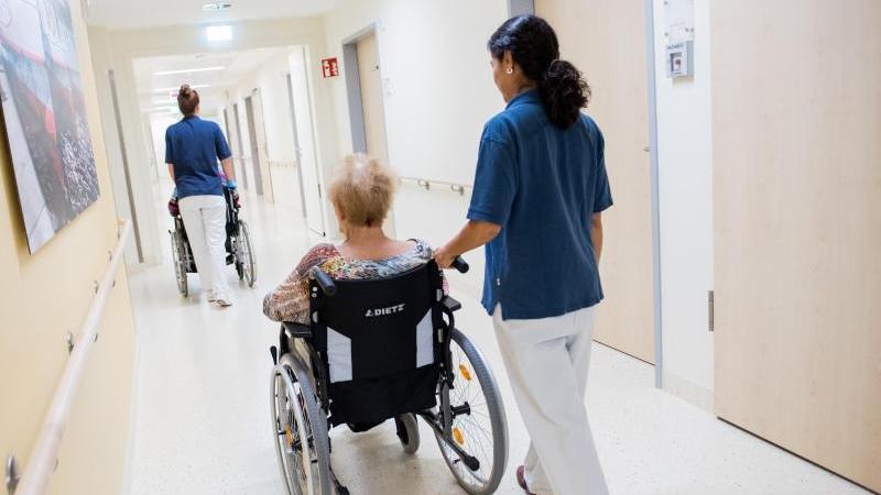 Zwei Pflegerinnen schieben in einem Klinikum Patienten mit Rollstühlen durch einen Flur. Foto: Daniel Bockwoldt/dpa/Symbolbild