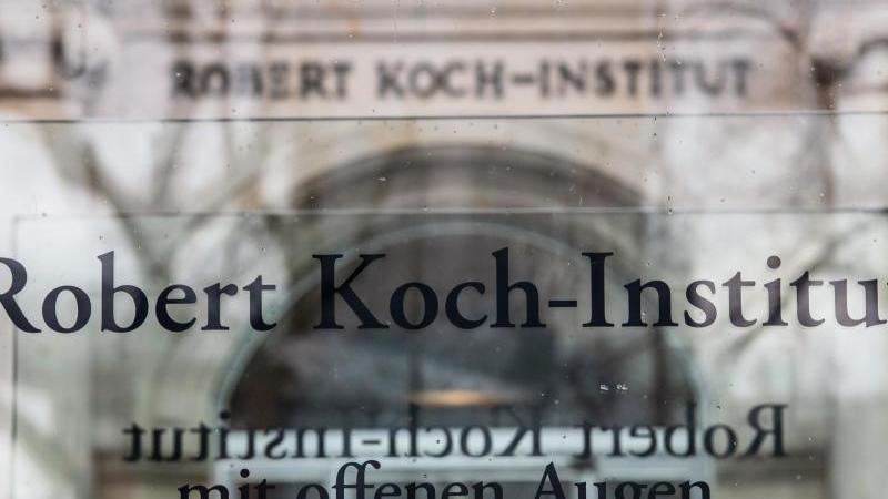 """""""Robert Koch-Institut"""" steht auf einem Schild vor dem Eingang des Instituts. Foto: Paul Zinken/dpa"""