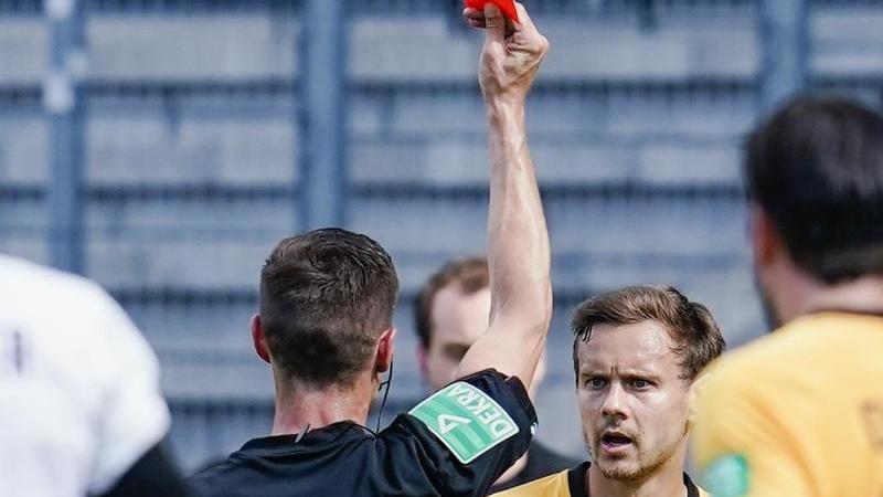 Schiedsrichter Robert Kempter zeigt Dresdens Chris Löwe die rote Karte. Foto: Uwe Anspach/dpa/Archivbild