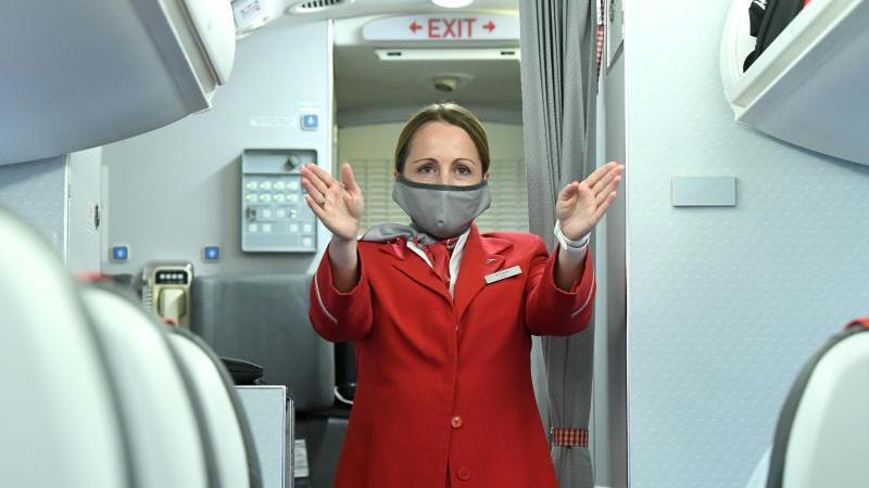 Nicht nur das Personal, auch Passagiere müssen auch im Flugzeug Masken tragen und alle Hygienemaßnahmen beachten. Foto: Helmut Fohringer/APA/dpa