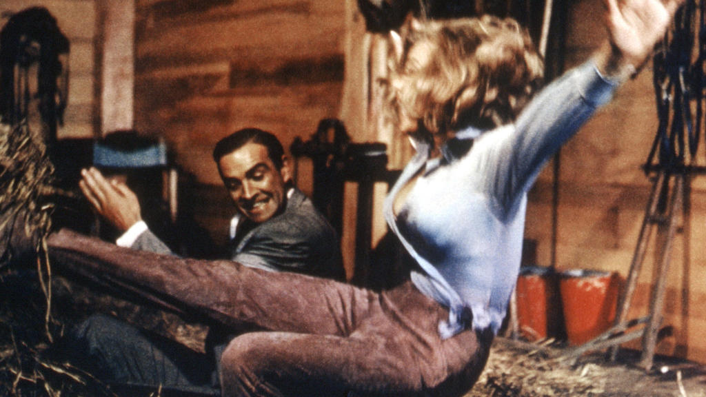 "Nicht zimperlich mit Pussy Galore (Honor Blackman): James Bond (Sean Connery) in ""Goldfinger"""