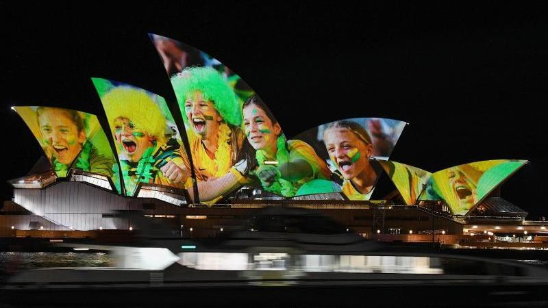 Australien und Neuseeland sind die Gastgeber der Frauenfußball-Weltmeisterschaft 2023: Das Opernhaus wird mit leuchtenden bunten Fotos von Fußball-Fans angestrahlt. Foto: Bianca De Marchi/AAP/dpa