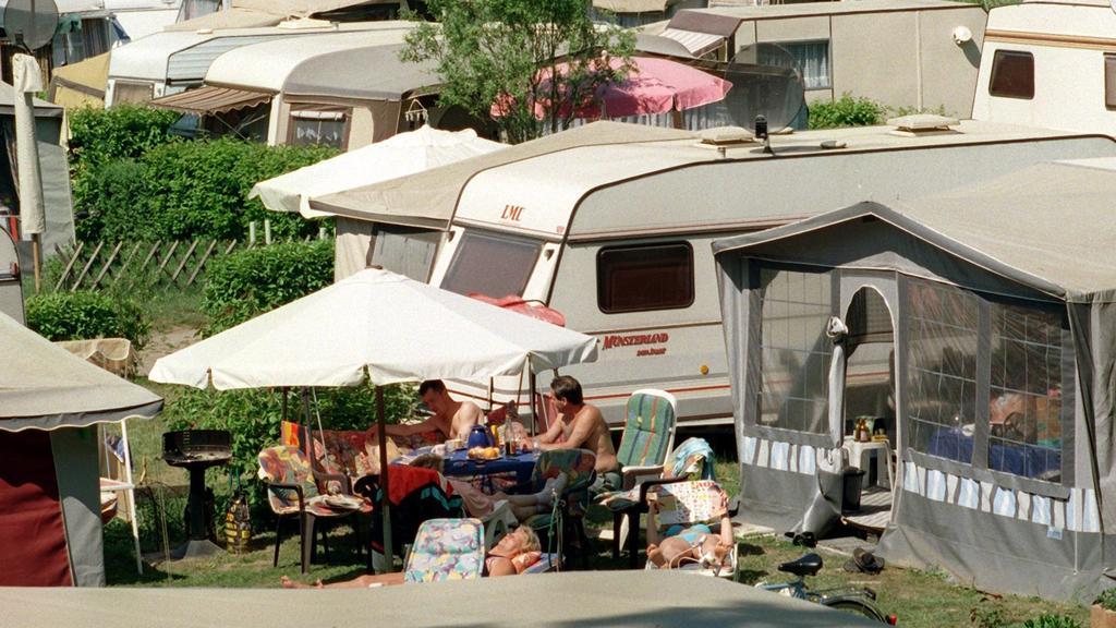ARCHIV - 08.05.2000, Berlin, Eichhorst: Dicht gedrängt genießen Camper an einem See die Sommersonne. Die Welt entdecken ohne auf Fahrpläne oder Hotels angewiesen zu sein, das fasziniert viele Menschen. Ein Zuhause auf Rädern bietet Mobilität und Bequ