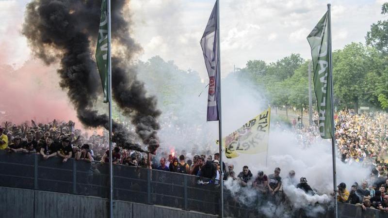 Dynamos Spieler werden nach dem Spiel vor dem Stadion mit Pyrotechnik gefeiert. Foto: Robert Michael/dpa-Zentralbild/dpa