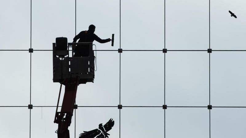 Ein Gebäudereiniger putzt die gläserne Fassade des World Trade Center (WTC) in Dresden. Foto: Sebastian Kahnert/dpa-Zentralbild/dpa