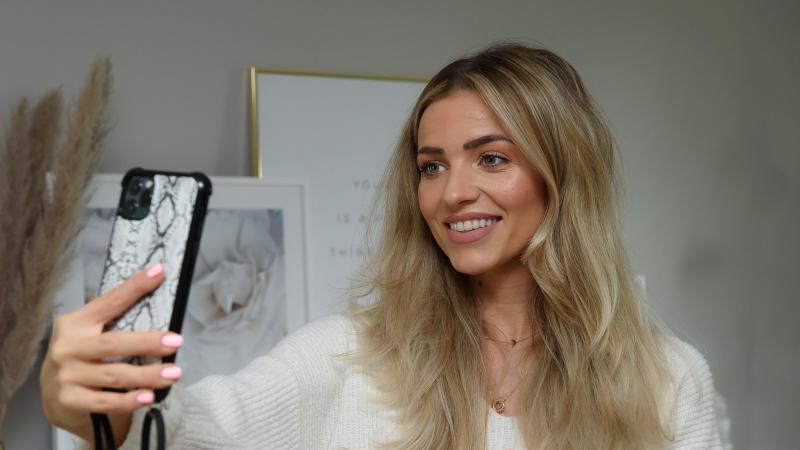 Influencerin Luana Theodoro da Silva (Luana Silva) bedient ihrem Arbeitszimmer ein Smartphone. Foto: Swen Pförtner/dpa