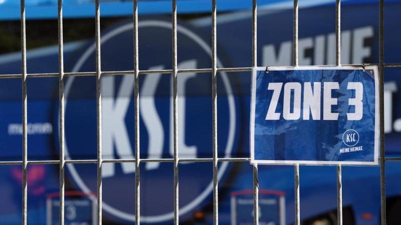 Das Logo des KSC ist hinter einem verschlossenen Tor zu sehen. Foto: Matthias Hangst/Getty Images Europe/Pool/dpa/Archivbild