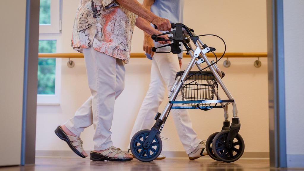ARCHIV - 23.08.2018, Stuttgart: Eine Pflegekraft geht in einem Pflegeheim mit einer älteren Dame über einen Korridor. (zu dpa «AOK-Zahlen zur Pflege in Rheinland-Pfalz») Foto: Christoph Schmidt/dpa +++ dpa-Bildfunk +++