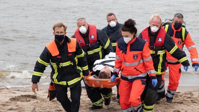 Rettungskräfte der Feuerwehr Hamburg tragen bei einer Übung einen Taucher zum Rettungswagen. Foto: Christian Charisius/dpa