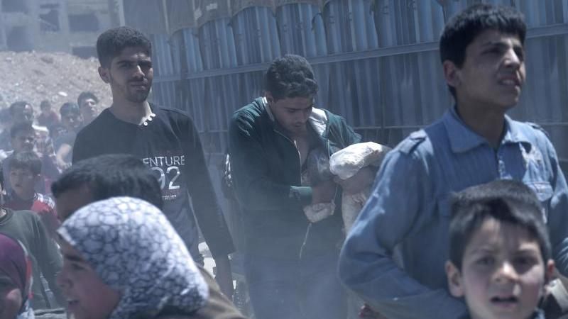Im syrischen Duma werden - hier im Jahr 2018 im Auftrag der Regierung - Lebensmittel ausgeteilt. Foto: Hassan Ammar/AP/dpa