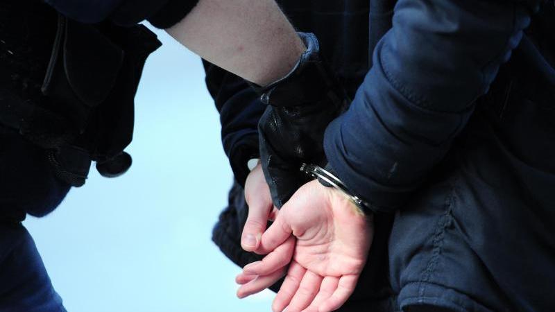 Ein Mann wird in Handschellen abgeführt. Foto: Daniel Reinhardt/dpa/Symbolbild