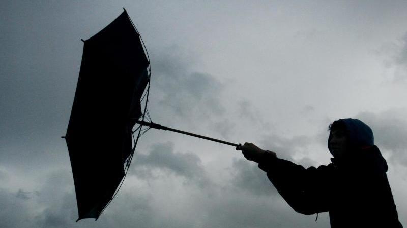 Ein Regenschirm eines Spaziergängers wird von einer Windböe erfasst. Foto: picture alliance / Karl-Josef Hildenbrand/dpa/Symbolbild
