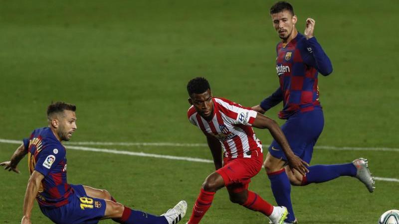 Jordi Alba (l) und Clement Lenglet (r) vom FC Barcelona gegen Thomas Lemar von Atletico Madrid. Foto: Joan Monfort/AP/dpa