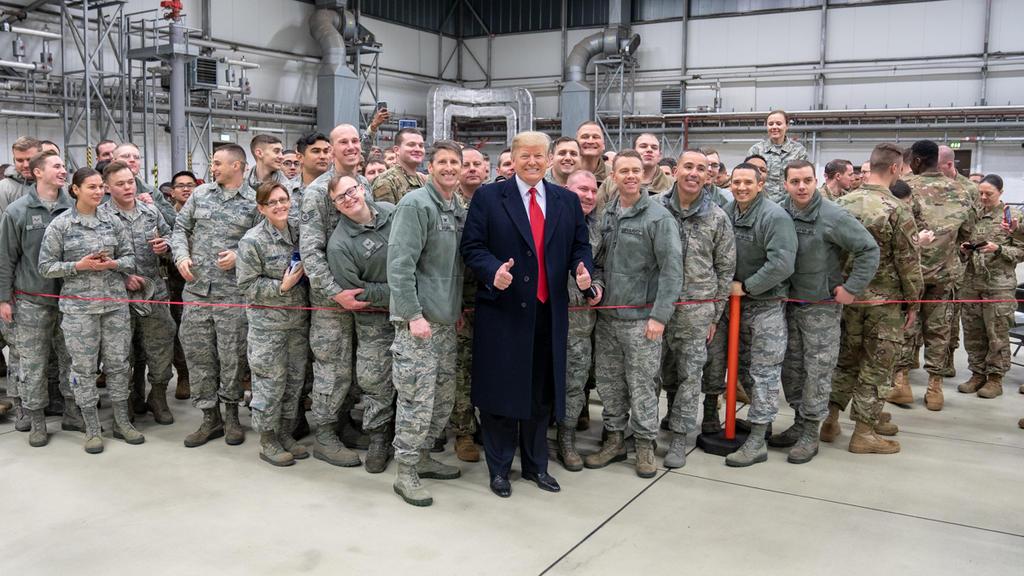 ARCHIV - 27.12.2018, Hessen, Ramstein: Donald Trump (M), Präsident der USA, lässt sich, während eines Zwischenstopps auf dem Stützpunkt der US-Luftwaffe in Ramstein, mit Militärangehörigen fotografieren. Der Abzug von rund 9500 US-Soldaten aus Deutsc