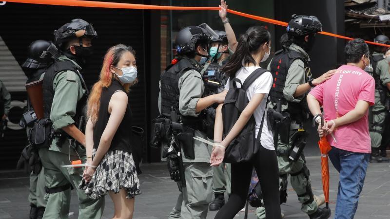 Polizisten führen Demonstranten mit am Rücken zusammengebundenen Händen ab. Foto: Kin Cheung/AP/dpa