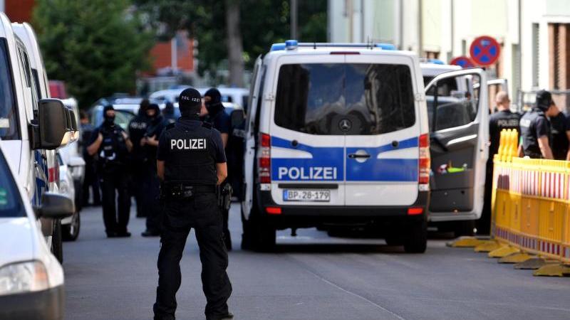 Einsatzkräfte von Polizei und Zoll stehen auf der Straße. Foto: Hendrik Schmidt/dpa-Zentralbild/dpa