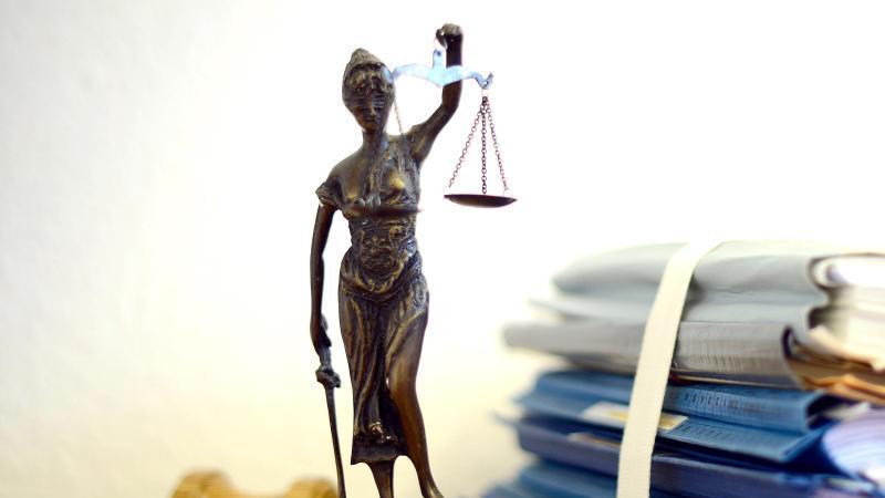 Eine Statue der Justitia steht neben Aktenbergen. Foto: Volker Hartmann/dpa/Archivbild