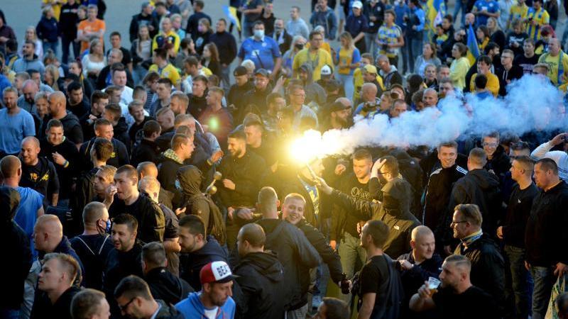 Braunschweiger Fans feiern vor dem Stadion mit der Mannschaft den Aufstieg. Foto: Hauke-Christian Dittrich/dpa