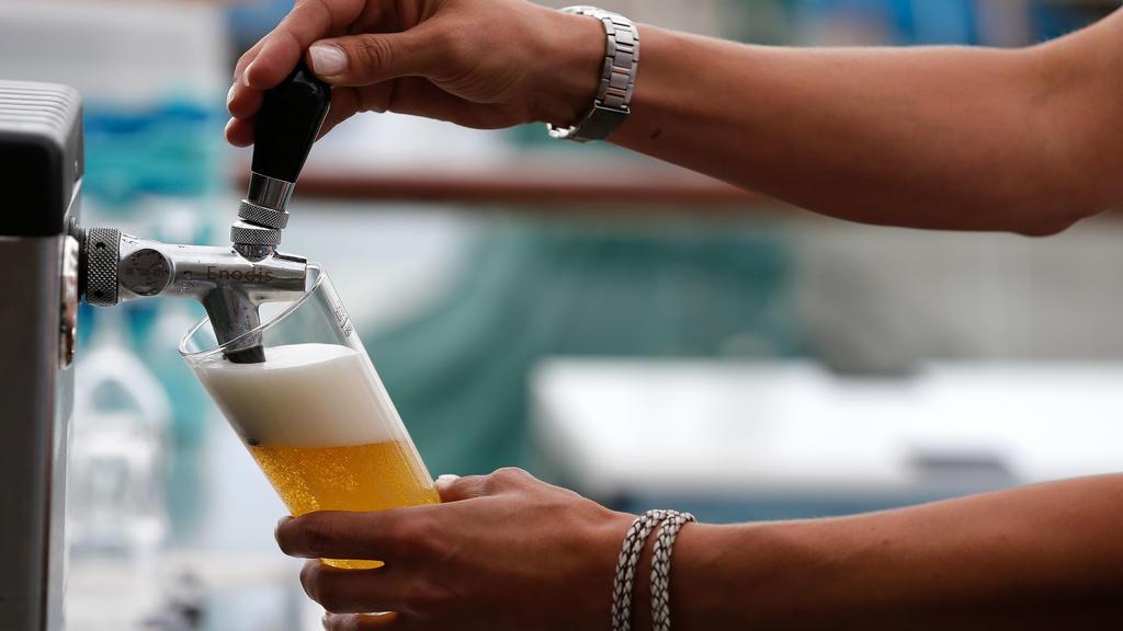 ARCHIV - 16.08.2013, Kiel: ARCHIV - Eine Servicekraft zapft in einer Gaststätte ein Bier. Minijobber sind Experten zufolge besonders hart von der Corona-Krise betroffen, da sie keinen Anspruch auf Kurzarbeitergeld haben. Foto: Axel Heimken/dpa +++ dp