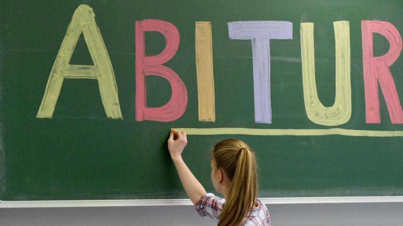 """Eine Schülerin unterstreicht das Wort """"Abitur"""" an der Tafel. Foto: picture alliance / dpa"""