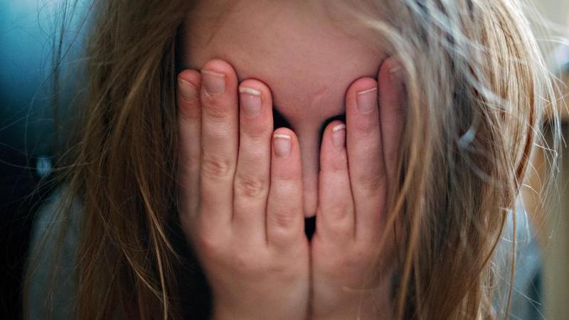 Ein junges Mädchen hält sich die Hände vor ihr Gesicht. Foto: Nicolas Armer/dpa/Symbolbild