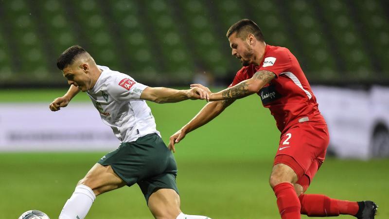 Werder-Profi Milot Rashica (l) wird vom Heidenheimer Marnon Busch verfolgt. Foto: Martin Meissner/AP POOL/dpa