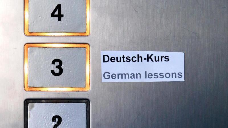 """Ein Schild """"Deutsch-Kurs"""" und """"German lessons"""" klebt im Fahrstuhl eines Gebäudes. Foto: Jan Woitas/dpa-Zentralbild/dpa/Symbolbild"""