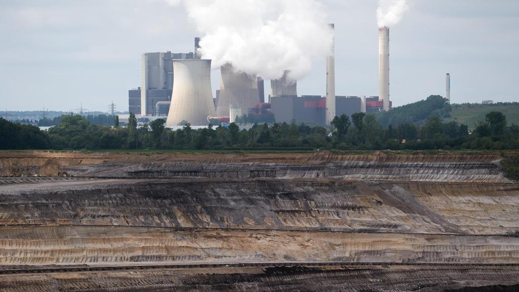 03.07.2020, Nordrhein-Westfalen, Schophoven: Hinter dem Braunkohletagebau Inden steht das Braunkohlekraftwerk Weisweiler. Bundestag und Bundesrat haben den schrittweisen Kohleausstieg in Deutschland bis spätestens 2038 beschlossen. Am Vormittag stimm